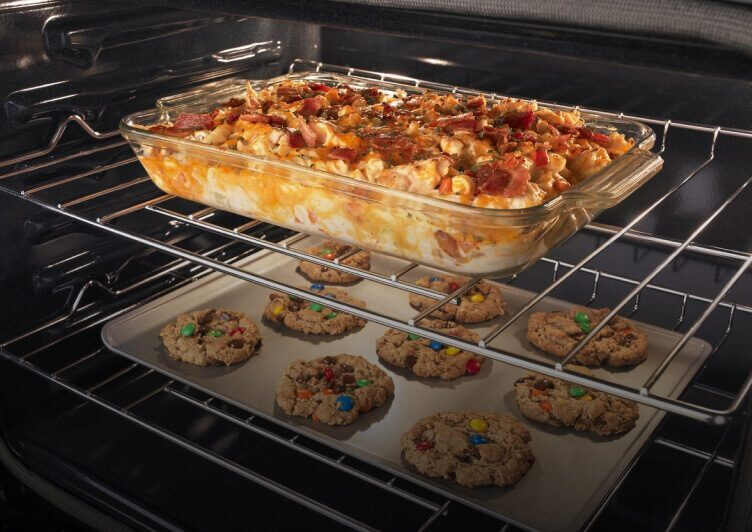 The inside an Amana® range baking cookies and a casserole.