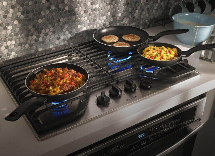 An Amana® cooktop with three burners cooking.